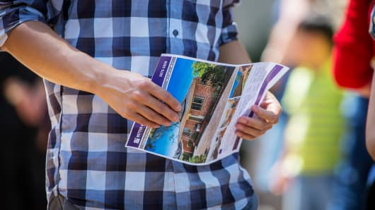 A prospective buyer holds a brochure after inspecting a house for sale in the suburb of Eastwood in Sydney, Australia.