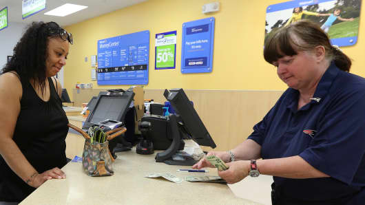 A Walmart employee facilitating a transaction for a Walmart money services customer in Massachusetts.