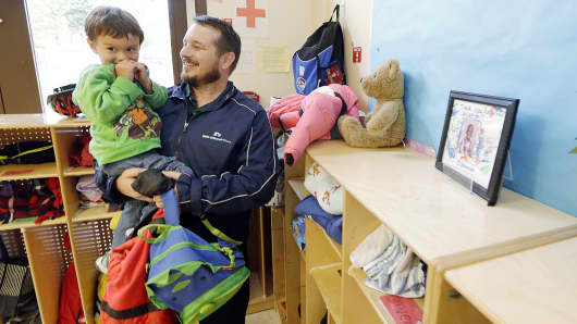 In this Sept. 18, 2014 photo, Jason Prosser picks up his son Zachary, 3, from day care, in SeaTac, Wash.