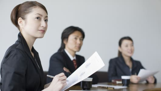 A Japanese female employee, with her colleagues, at a meeting.