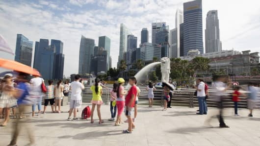 Tourists gather at the Merlion statue along the Singapore River.