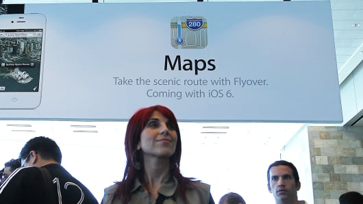 WWDC attendees walk by a poster for the new Maps application at the Apple 2012 World Wide Developers Conference (WWDC) at Moscone West on June 11, 2012 in San Francisco.