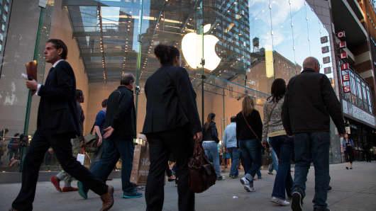 Pedestrians walk by an Apple store in New York.
