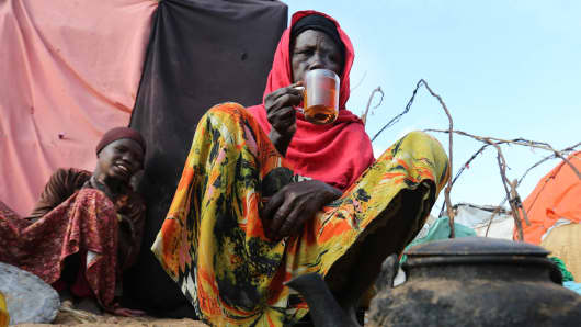A displaced Somali woman sits outside her temporary dwelling after fleeing famine