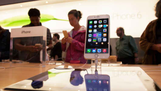 Shoppers look at iPhones at an Apple store in New York
