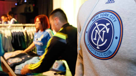 Sales people arrange team merchandise as they begin sales after the new MLS franchise New York City Football Club unveiled their new team badge in New York.