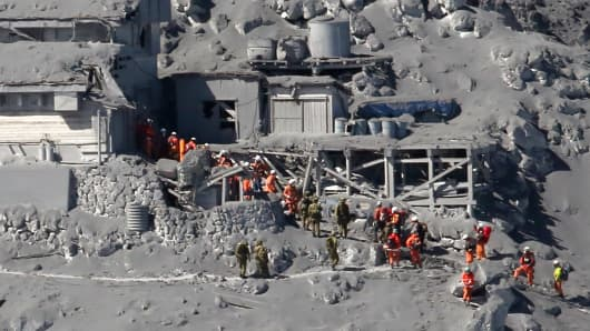 This aerial picture taken on September 28, 2014 shows rescue workers and Self Defence Force soldiers searching for missing climbers and survivors among ash covered mountain cottages on the top of Mount Ontake at Nagano prefecture.