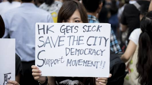 A woman holds a protest sign at a pro-democracy protest on Nathan Road, a major route through the heart of the Kowloon district of Hong Kong.