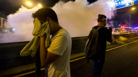 A protester covers his face as riot police fire teargas after thousands of demonstrators blocked the main street to the financial district Central in Hong Kong on Sept. 28, 2014.
