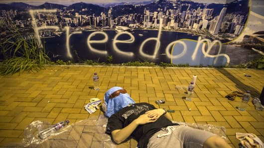 A protester sleeps on the streets outside the Hong Kong Government Complex at sunrise on September 30, 2014 in Hong Kong.