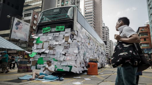 A man walks past a pro-democracy demonstrator guarding a bus placarded with messages of support in Hong Kong on September 30, 2014.