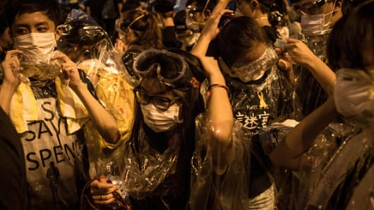 Protesters put on goggles and wrap themselves in clear wrap after hearing a rumour that police were coming with tear gas outside the Hong Kong Government Complex on September 29, 2014 in Hong Kong,
