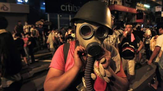 A protester puts on a gas mask to prepare for a possible tear gas attack as hundreds of protesters block a main road at Hong Kong's shopping Mongkok district September 29, 2014.
