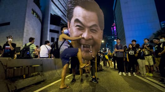A protester hits a defaced cutout of Hong Kong Chief Executive Leung Chun-ying, as they protest near the central government offices in the business district of Admiralty in Hong Kong September 29, 2014.