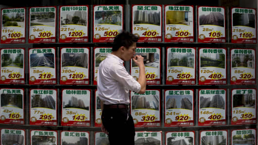 A man walks in front of advertisements for residential property in the glass facade of a real estate agency in Guangzhou, Guangdong province of China.