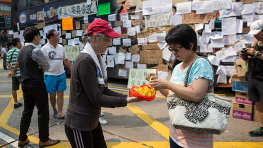 A demonstrator, left, hands out yellow ribbons to supporters in front of an immobilized bus covered with signs at the intersection of Nathan Road and Mongkok Street in the area of Mongkok in Hong Kong, China.