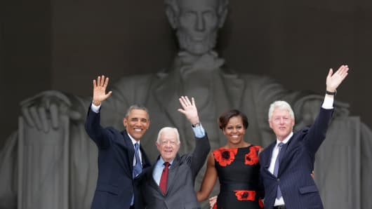 President Barack Obama, former president Jimmy Carter, first lady Michelle Obama, and former president Bill Clinton wave