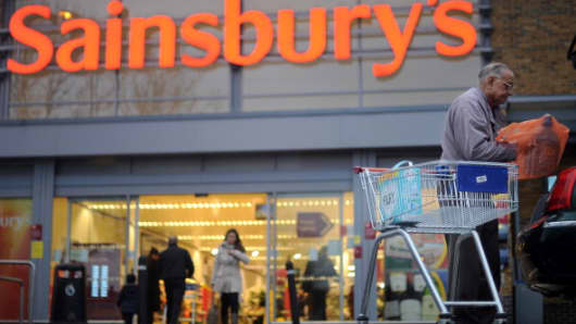 A man puts a shopping bag into a car outside a Sainsbury's store in London