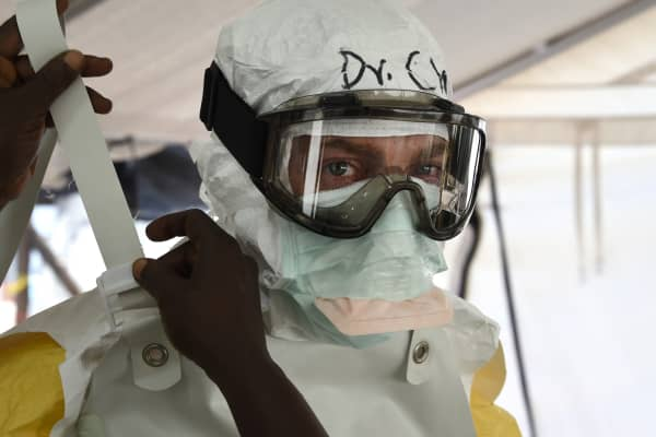 A health worker helps a doctor to fix his protective suit, on October 1, 2014 at MSF's (Doctors Without Borders) Ebola treatment center in Monrovia. Liberia.