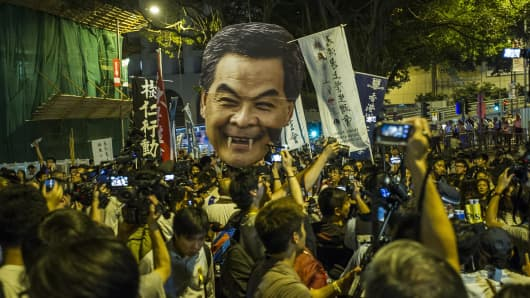 Students march to the Government House in Hong Kong holding a portrait of Chief Executive Leung Chun Ying.