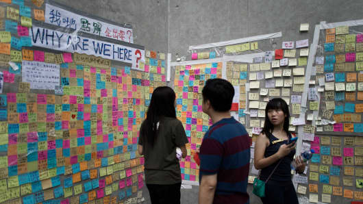 People look at messages of support displayed on a post-it wall outside the government headquarters in Hong Kong.