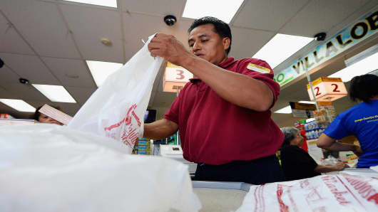 A clerk bags groceries with plastic bags in Los Angeles.