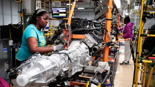 A Chrysler assembly line employee in Warren, Mich., works on a Ram 1500 transmission, Sept. 25, 2014.