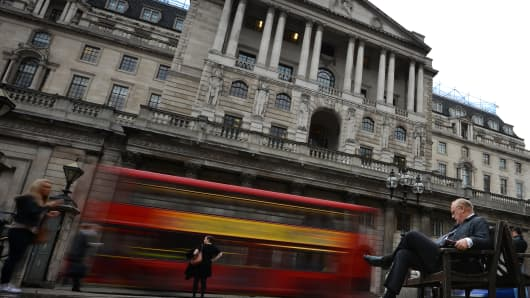 A man sits on a bench outside the Bank of England in London.
