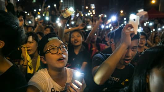 Student protesters hold their cell phone lights chanting pro democracy slogans during evening speeches at the protest site on October 1, 2014 in Hong Kong, Hong Kong.