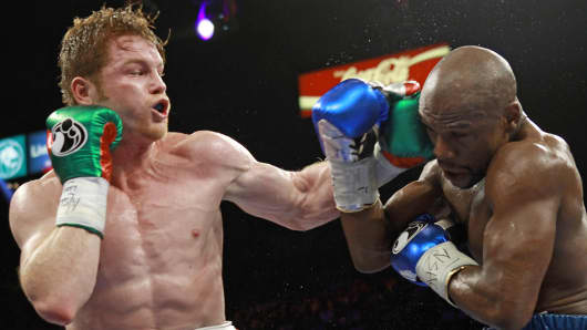 Canelo Alvarez, left, throws a punch against Floyd Mayweather Jr. during a 152-pound title fight, Sept. 14, 2013, in Las Vegas.