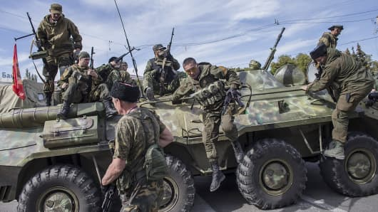 Pro-Russian rebels jump off an armored personnel carrier during a parade in Luhansk, eastern Ukraine.