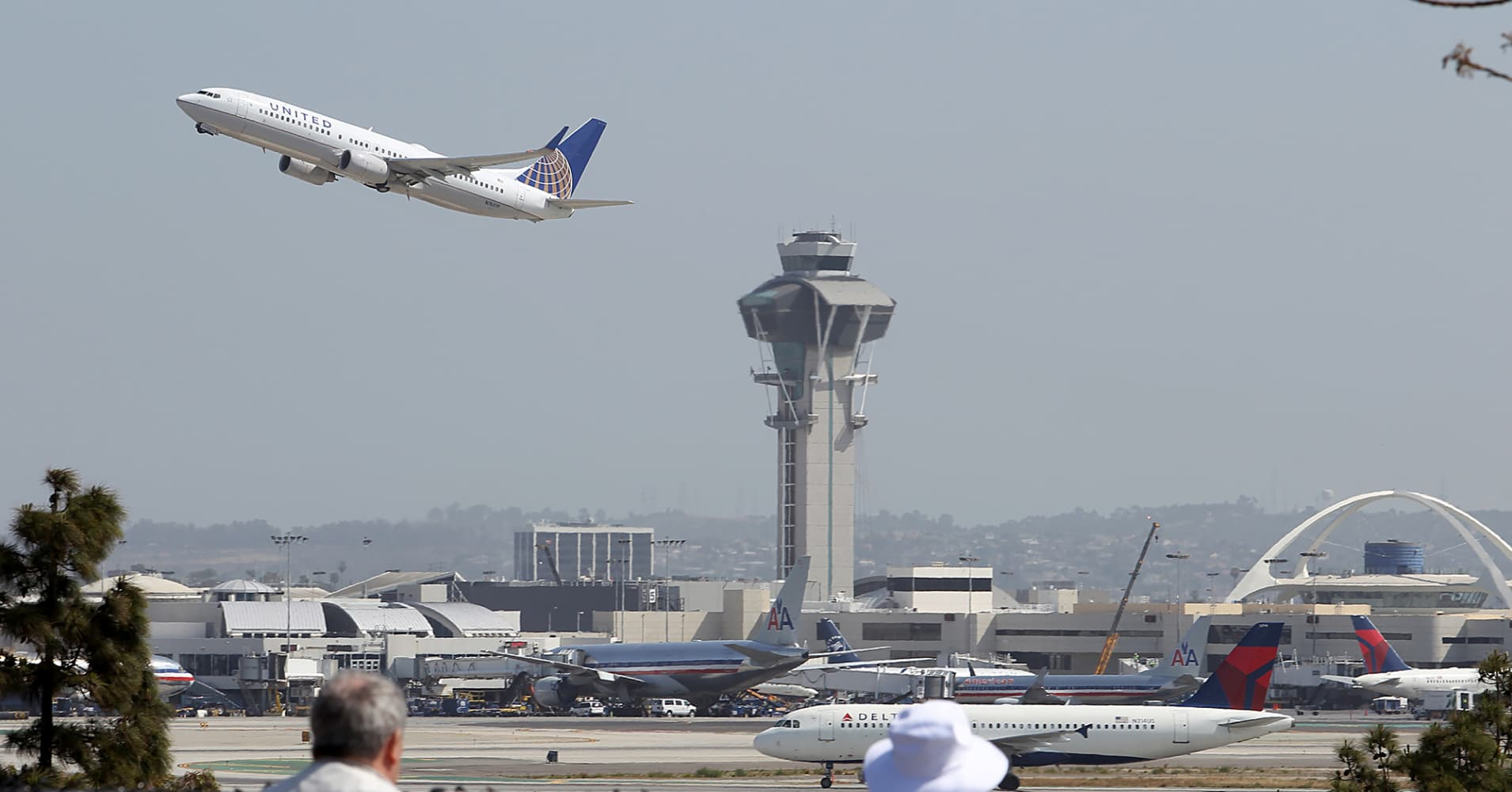 People watch as a United Airlines jet passes the air traffic control tower at Los Angles International Airport during takeoff.