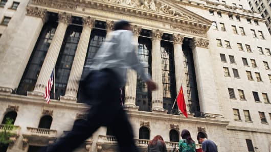 People walk past the New York Stock Exchange, May 21, 2014.