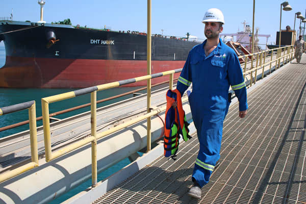 An Iraqi worker walks past a tanker docked at a floating platform on offshore from the southern Iraqi port city of Al Faw.
