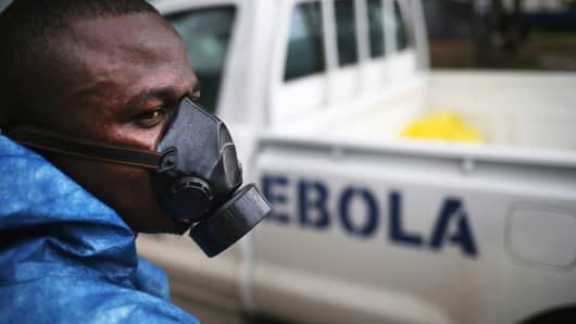 A health worker watches as a burial team collects Ebola victims from a Ministry of Health treatment center for cremation on October 2, 2014 in Monrovia, Liberia.