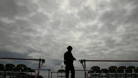 A Japan Ground Self-Defense Force (JGSDF) officer stands as typhoon Phanfone rainstorm darkens the sky during the annual Japan Ground Self-Defense Force military demonstration.