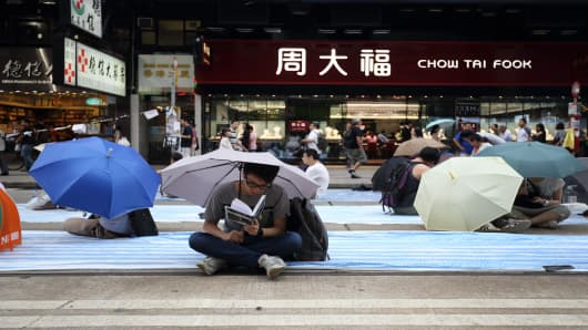A demonstrator reads a book as he sits holding an umbrella along with other demonstrators in front of a Chow Tai Fook Jewellery Group Ltd. store during a protest in the Causeway Bay area of Hong Kong, on Saturday, Oct. 4, 2014.