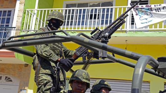 Mexican soldiers patrol the street of Tepacalcatepec in the state of Michoacan, Mexico, on February 13, 2014.