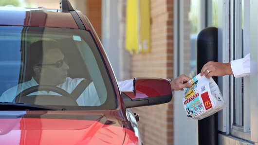 An employee hands a drive-thru customer his food order a McDonald's Corp. restaurant in Oak Brook, Illinois.