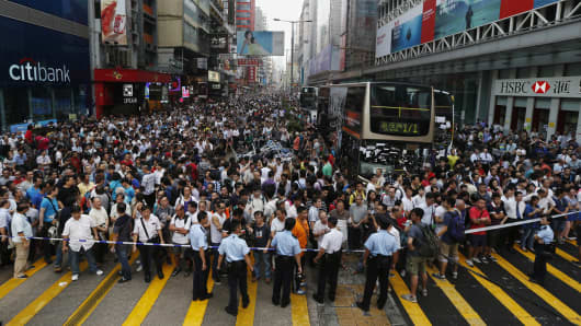 Anti-Occupy Central protesters stand behind a police cordon on Nathan Road at Hong Kong's Mongkok shopping district October 3, 2014.