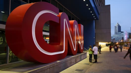 Pedestrians pass in front of CNN signage displayed at the network's headquarters building in Atlanta.