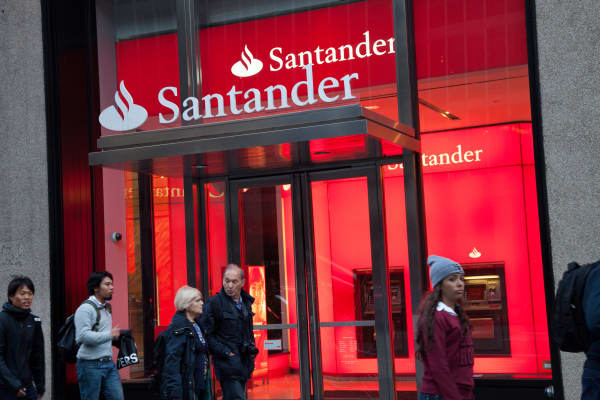 Pedestrians pass by a Santander Bank branch in New York.
