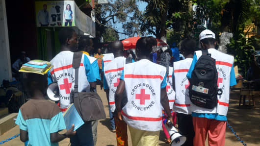 Members of the Guinean Red Cross walk during an awareness campaign on the Ebola virus on April 11, 2014 in Conakry, Guinea.