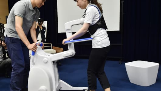 Models demonstrate a robot assistant to support people walking and standing up from a bed and moving to the toilet, during a press preview hosted by Japan's Panasonic in Tokyo.