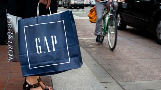 A pedestrian carries a Gap shopping bag in San Francisco.