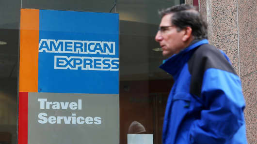 A pedestrian walks by an American Express Travel Services office in San Francisco.