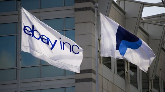 PayPal and eBay flags fly in front of the company's headquarters in San Jose, Calif.