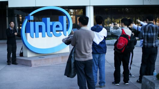 Visitors take pictures next to the Intel logo at Intel headquarters in Santa Clara, Calif.
