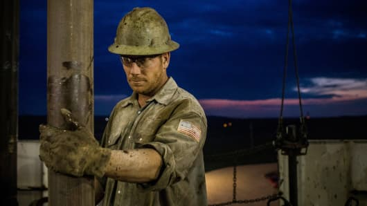 A derrick hand works on an oil rig drilling into the Bakken shale formation outside Watford City, N.D.