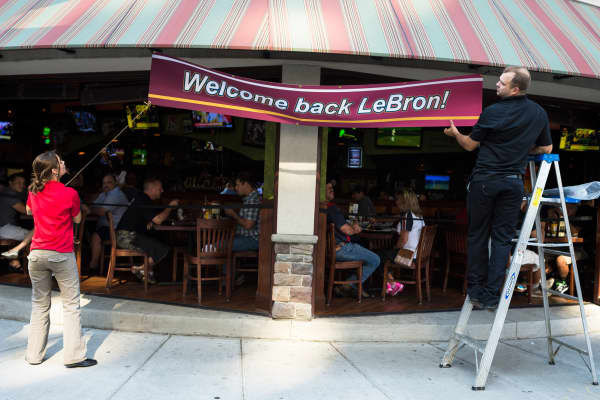 Employees of The Tilted Kilt in Cleveland hang a banner to welcome back LeBron James after his announcement in July.